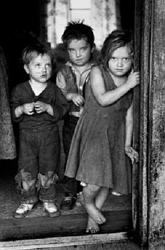 Children of a disabled coal miner stand in the doorway of their Appalachian home in the early 1930's by Jack Corn