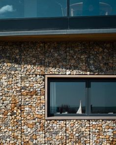 The base of this house is clad with gabions, lending it a density that roots it in the landscape.