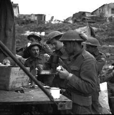 Personnel of the Loyal Edmonton Regiment having tea and sandwiches outside Battalion Headquarters, Ortona, Italy, 21 December 1943.