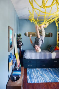 This boy& bedroom is bright and full of fun with surfboards and skateboards all over the place – but what is that on the ceiling? A yellow net is attached for climbing, flipping, and general fun. What a cool idea for those busy kids who like to climb! Master Bedroom Closet, Girls Bedroom, Trendy Bedroom, 4 Year Old Boy Bedroom, Diy Bedroom, Teen Boy Rooms, Bedroom Beach, Bedroom Decor For Boys, Bedroom Wall