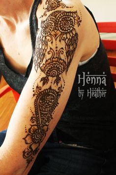 An owl henna design with Indian flare on the arm.