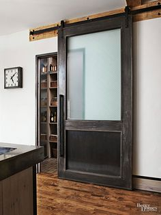 One way to easily mix reclaimed woods of different types and styles is to create color contrast. Here, that's done with ease—a pretty reclaimed wood floor in a richly natural stain, and a hefty oversize door stained a rich black-brown and recast as a sliding pantry door./