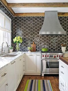 Oblong charcoal tiles pop with cream-color grout. The kitchen stays light and bright with white quartz-surfacing counters, cream-color cabinetry, and a rustic wood beam ceiling. Love the shape❤️