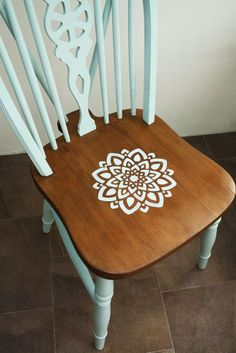 Lovely pine farmhouse dining chair, painted in duck egg blue with a hand-stencilled mandala flower design on the seat. This chair was in a bit of a sorry state when it came to me - the joints were loose and repairs had been attempted, but ultimately the chair was abandoned. I carefully took it apart and cleaned and sanded each joint, then sanded each piece back to the original wood. I re-glued all of the joints to make it sturdy again, then set about giving it a new paint job. The seat of…