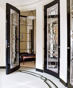 In a Manhattan apartment designed by David Kleinberg, the entrance hall features ebonized-mahogany doors inset with mirror and silver-plate grillwork; the silver door hardware is by Nanz