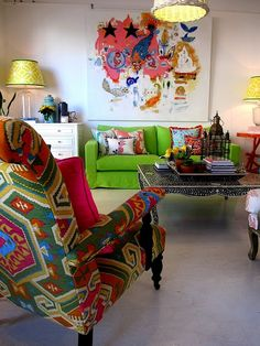 Colorful living room. Absolutely love the small chair table and wall art..don't know how I feel about the green couch though..it definitely works though