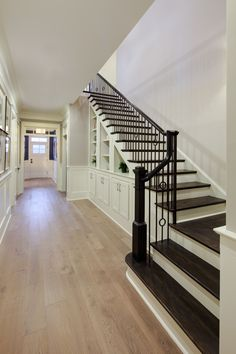 There are two design choices that really stand out in this picture. The first is the wonderful contrast between the light hardwood flooring used in the hallway and the dark hardwood flooring used on the stairs. The second is the handrail style used Hardwood Floor Colors, Hardwood Stairs, Flooring For Stairs, Light Hardwood Floors, White Oak Floors, Dark Hardwood, Dark Staircase, Staircase Design, Staircase Ideas