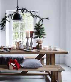 White colours, casual decorations and muted colours create the perfect backdrop for an easy and informal scheme. This laid-back look with bench seating, soft textures and festive greenery sets the scene for convivial dining. Table, bench, pendant, tree and garland by @neptunehomeofficial. --- #dining #diningtable #festive #interior