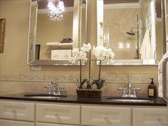 LOVE THIS!                                                Cream bathroom cabinets, silver beveled bevel mirrors and black granite countertops! Love chandeliers in bathrooms! Cream black bathroom. black cream ivory bathroom colors.