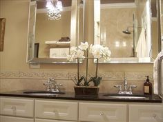 LOVE THIS!                                                Cream bathroom cabinets, silver beveled bevel mirrors and black granite countertops! Love chandeliers in bathrooms! Cream black bathroom. black cream ivory bathroom colors.