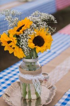 A picnic-themed reception table setting with burlap runners, and mason jar centerpieces with baby's breath and sunflowers!