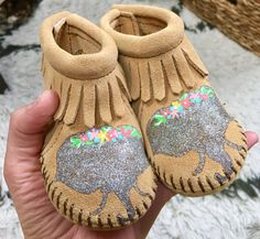 Because elephants and glitter and floral crowns. Custom elephant silhouette in shimmering silver glitter with flower crowns handpainted on Minnetonka leather moccasins size 1 infant through 6. Custom and one-of-a-kind, painted by me. I can paint different colors or animals to coordinate with nursery or baby shower themes. Free Range Mama is a free-hand, completely custom, hand-painted collection of keepsake baby booties and moccasins! My personalized shoes make the best baby shower gifts…