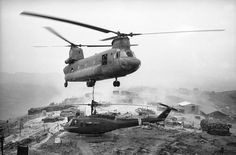 """At a hilltop firebase west of Chu Lai in Vietnam, a huge army """"Chinook"""" helicopter prepares to lift a conked-out smaller one to a base for repairs, April 27, 1969. The firebase was named LZ West and was manned by the troopers of the 196th Light Infantry Brigade forming part of the American Division. The smaller helicopter - a Huey UH-ID - had developed engine trouble so its crew chief called in the local aerial towing service. One sturdy nylon strap to the chopper's winch and the two were…"""
