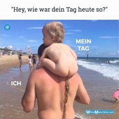 Kind kackt am Strand auf Papas Rücken