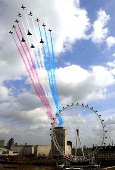 The Red Arrows fly over London. (Those look like 4 Typhoons accompanying the Red Arrows.)