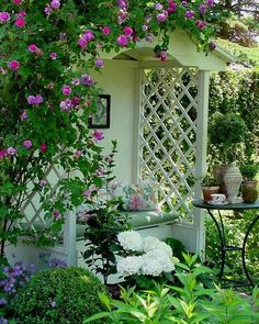 Romantic covered garden bench!!! Bebe'!!! Surrounded by dark pink climbing roses and some green plants in containers and a pretty white ginger jar with a lid!!!