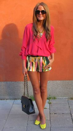 bright pink ruffle blouse, patterned shorts, Chanel bag, and neon yellow flats.