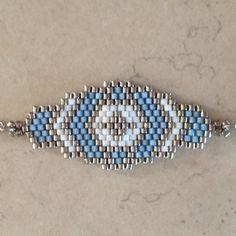 Bracelet en perles MIYUKI 11 délicas blanc, argent et bleu Tissage à la main avec une aiguille Dimensions hors accroche : 4 x 2 cm Fermoir mousqueton et chaîne acier inox Longueur : 18 cm Vous pouvez lavoir dans la longueur que vous désirez , il suffit de me le préciser à la