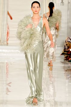 3/1/15 This light olive green dress is reminiscent of the 1920s. The dropped waist, feathered boa, and tubular silhouette are all indicators of this time. This Ralph Lauren dress is also inspired by this time because of the elegant and straight look.