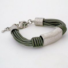 "Silver Leather & Silver Tube Bracelet Escape From Paris. $45.00. Center tube is approx. 1/2"" wide. industrial antique silver tube at center. 7"" in length, 1 3/4"" extender,  lobster clas. Multiple silver leather strands. Ends are finished with short silver tubes"