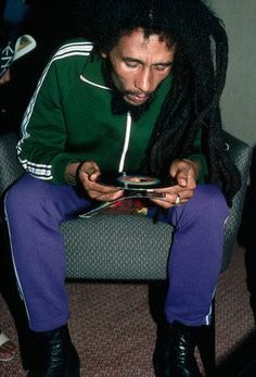 Bob Marley's examines the label of a single