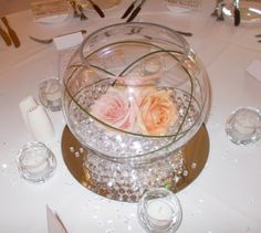 Fishbowl with pale pink and peach roses and beargrass