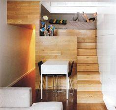 persona recostada sobre una cama que esta casi llegando al techo y bajo de ella esta el comedor y una pequeña sala