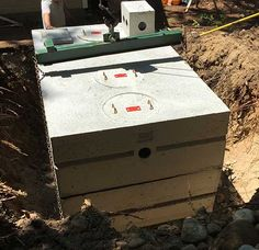 Photo of precast concrete septic tank being placed in the ground.