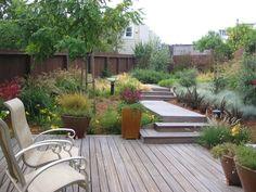 terrasse ensoleillée en bois aménagée avec chaises métalliques et jardinières originales