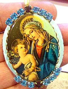 $69 Blue enamel Oval Locket with Blue and brown rhinestones, acrylic center cameo depicting The Virgin mary and the Baby Jesus Christ.   Locket can hold 2 photo's. Interior is copper and brass.  Goldtone bail.