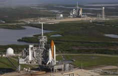 Space shuttle Atlantis (foreground) sits on Launch Pad A and Endeavour on Launch Pad B at NASA's Kennedy Space Center in Florida on September 20th, 2008. At the left of each shuttle are the open rotating service structures with the payload changeout rooms revealed. The rotating service structures provide protection for weather and access to the shuttle. For the first time since July 2001, two shuttles are on the launch pads at the same time at the center. Endeavour will stand by at pad B in…