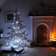 Un árbol de madera con luces blancas. Cuando se acaben las fiestas, simplemente tienes que desarmarlo y será fácil de guardar.