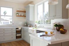 Light Green Cabinets, baskets, floating shelves, caesar stone. Farmhouse sink