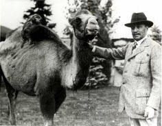 Spencer Penrose with his camel and the monkey on the camel's back.