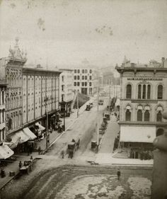 A snowy Campau Square with Powers Opera House Block left of center. In the winter of 1882–83 while the Houseman Block at the corner of Ottawa and Pearl Street was under construction. Photo taken from side of clock tower atop Col. E. S. Pierce Clothing Tower Block at the juncture of Pearl Street, Monroe and Canal.