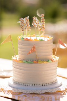 inspiration | wedding cake with mini flags and confetti monogram cake toppers | via: one fab day