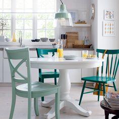 On préfère créer un espace qui traversera le temps? Des armoires blanches et un mobilier aux lignes classiques s'avèrent un bon choix. Ce modèle de table séduit depuis toujours et s'adapte aux tendances si on en change la couleur. La table ronde est d'ailleurs un choix judicieux si on ne possède pas de salle à manger, car elle permet d'accueillir jusqu'à six convives. Pour une touche d'originalité, on installe des chaises dépareillées.