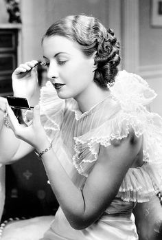Barbara Stanwyck applying makeup