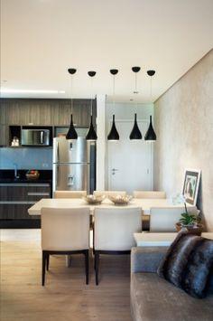 Na proposta da arquiteta Izabela Lessa, o living (17 m²) está integrado à cozinha. Aqui, o destaque fica por conta da parede espelhada que apoia o painel da TV. A marcenaria também faz a diferença: cria um aparador com gaveteiro e uma pequena bancada que abriga sob si os pufes, que podem ser usados em pequenas refeições ou em eventos sociais