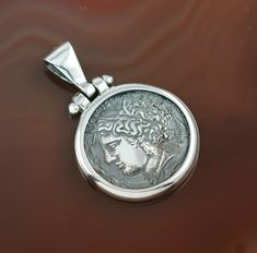 """""""Arethusa"""" pendant - a silver replica of one of the most famous, beautiful and universally admired coins ever made (minted by the city of Syracuse, around 400 BC).  The coin represents Arethusa - the water nymph, the patron deity of Syracuse.  Arethusa symbolizes feminine energy, constantly flowing stream, elusive before masculine force.  She is the personification of a great mystery, which is every woman for a man."""