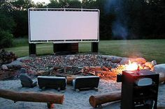 outdoor movie theater with large screen and log seating