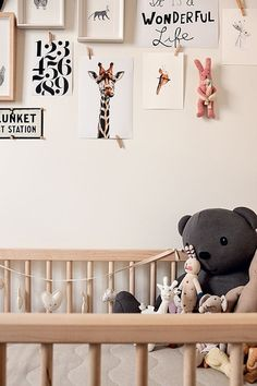 Adorable gender neutral nursery with light wooden crib laden with stuffed animals below a gallery wall with framed art and frameless prints pinned by tiny wooden pegs.