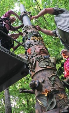 Pottery-class students from a nearby community college install their ceramic pieces on a totem pole sculpture at the N.C. Zoo. They later donated the completed sculpture to the zoo.