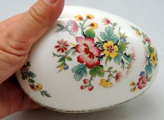 This Coalport Ming Rose Pattern Egg Jewelry/Trinket Box is in perfect condition. Beautiful piece. There is a bottom and a lid, so there are 2 pieces. It can be really used for anything you desire, since its quite deep due to its egg shape.  Size: 5 1/4 inches long at the point where lid meets bottom.  Feel free to browse my shop for other treasures at vinteclectic.etsy.com  Shipping prices vary by location and sometimes by item. I will refund a difference of $2 or more, should the postage…