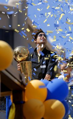 Warriors' Stephen Curry holds the championship trophy as he rides with his daughter Riley and wife Ayesha as the 2015 NBA champions Golden State Warriors  celebrate with a parade in downtown Oakland, Calif. on Fri. June 19, 2015.