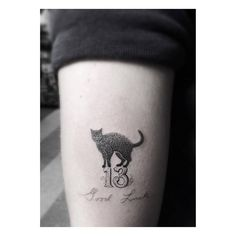"""Forearm tattoo of a black cat on top of the number 13 and the phrase """"Good luck."""" Tattoo artist: Dr. Woo"""