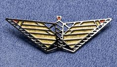 Wright Butterfly Pin--Artist: Frank Lloyd Wright®---Take flight with Wright. The Prairie School was characterized by simplicity of form with minimal embellishment, as is evident in this hematite plated brass and golden enamel butterfly pin. The soaring design is inspired by Frank Lloyd Wright's® (American, 1867-1959) window design for the Susan Lawrence Dana House in Springfield, Illinois.