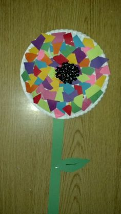 Preschool craft spring flower: paper plate, construction paper black beans, Elmer's glue