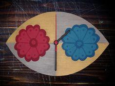 Açıklama: Çiçek desenli boyama. Teknik: Ahşap boyama. Malzeme: Parke. İşlemler: Eliptik kesim ve mat vernik. Saat tipi: Sessiz akar saat. Bütün ölçü: 29,5 cm en, 18 cm boy.