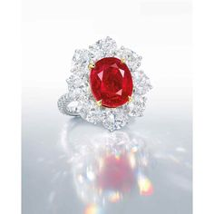 A SUPERB RUBY AND DIAMOND RING, BY FAIDEE The oval-shaped ruby, weighing approximately 10.05 carats, within a radiating surround of oval-shaped diamonds, to the circular-cut diamond gallery, extending to the undulating hoop, mounted in platinum and gold, ring size 6¼ Signed and with maker's mark for Faidee
